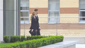 Two business colleagues walking on the street of an business center, slow motion. Two business colleagues in discussion, businesspeople walking on the street of stock footage