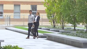 Two business colleagues walking on the street of an business center. slow motion. Two business colleagues in discussion, businesspeople walking on the street of stock footage