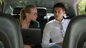 Two business colleagues working with laptop in car. Handsome young businessman in formalwear and businesswoman working on laptop computer while riding at the stock footage