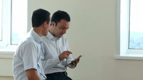 Two business executives sitting in a bright office space, looking for information together by sharing the screen of a stock video