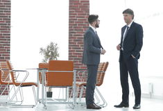 Two business executives talking about business in the office. Two business partners talking about business in the office royalty free stock images