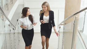 Two business girls climb the stairs of the office building communicating with each other. Slow motion stock video