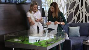 Two business girls looking at a mock office building in an office. Two beautiful business girls watching a mock-up of a business building and discussing business stock video