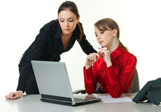 Two business ladies. Two young business ladies looking at the laptop screen stock photo