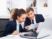 Two business male and female assistants wearing formalwear having work conversation. Two cheerful glad positive business male and female assistants wearing royalty free stock photo