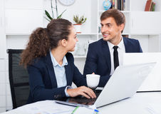 Two business male and female assistants wearing formalwear havin. Two  glad smiling business male and female assistants wearing formalwear having work Royalty Free Stock Photography