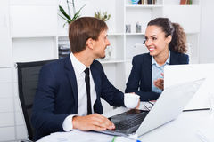 Two business male and female assistants wearing formalwear havin. Two smiling business male and female assistants wearing formalwear having work conversation in Stock Photography