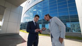 Two business man exchanging business cards and talking.  stock video