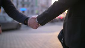 Two Business man handshake with blurred city background. Business handshake with blurred city background. Two businessmen greeting each other in urban stock video footage