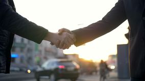 Two Business man handshake with blurred city background. Business handshake with blurred city background. Two businessmen greeting each other in urban stock video