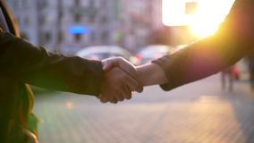 Two Business man handshake with blurred city background. Business handshake with blurred city background. Two businessmen greeting each other in urban stock footage