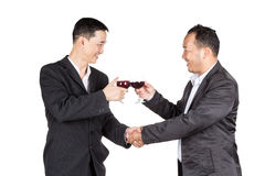 Two business man Holding a glass of wine and handshaking Royalty Free Stock Photos