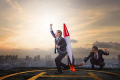 Two business man playing rocket toy on high building roof with s Royalty Free Stock Photography