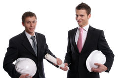 Two business man with safety hats, exchanging a ne. W project, isolated in white background royalty free stock image