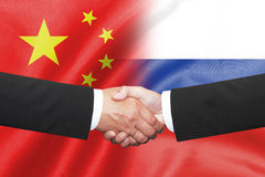 Two business man shakehand on china and russian flag. Isolated two business man shakehand on china and russian flag Stock Photos