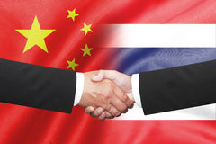 Two business man shakehand. Two business man shakehand over thai and china flag Royalty Free Stock Photography