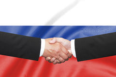 Two business man shakehand. Two business man shakehand on russian flag background Royalty Free Stock Images