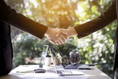 Two business man shaking hands during meeting in office with lap stock images