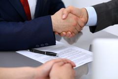 Two business man shaking hands to each other above signed contract Royalty Free Stock Photography