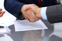Two business man shaking hands to each other above signed contract Royalty Free Stock Photos