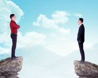 Two business man standing on the top of the mountain. Two business men standing on the top of the mountain. Business competition concept Stock Photo