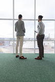 Two Business Man Using Tablet Computer Coworking Center Business Team Coworkers Stand in front Big Panoramic Window Royalty Free Stock Photo