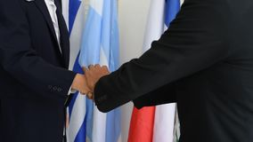 Two business mans or politicians shake hands during international conferences in front of different country flags stock footage