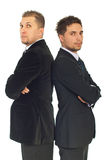 Two business men. In suits standing with arms folded back to back isolated on white background Royalty Free Stock Images