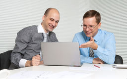 Two business men. Working on a laptop in office. Teamwork Royalty Free Stock Photo