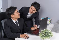 Two business man laughing while using laptop computer Stock Photography