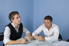 Two business men at meeting. Two business men sitting on chair at a meeting,one of them speaking and the other listening him and smiling,check also Business Stock Image