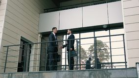 Two business men meeting at the entrance of business center and shaking hands to greet each other. And talk about their business. Slow motion stock footage