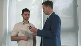 Two business men near the windows talking. Chief says employee gesturing and holding a mobile phone. Young mixed race man listening attentively stock footage