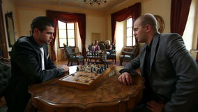 Two business men playing chess in a old fashioned restaurant stock footage