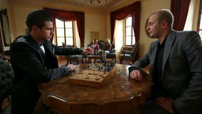 Two business men playing chess in an old fashioned restaurant stock footage