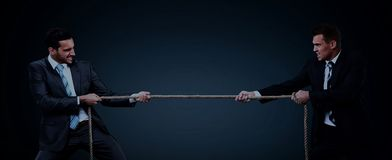 Two business men pulling rope in a competition. On dark background Royalty Free Stock Images