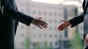 Two business men shake hands against business center background. Close-up shot. Slow motion stock video