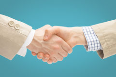 Two business men shaking hands - close up studio shot on light blue background Royalty Free Stock Photos