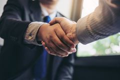 Two business men shaking hands during a meeting to sign agreement and become a business