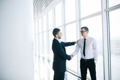 Two business men shaking hands in office stock photo