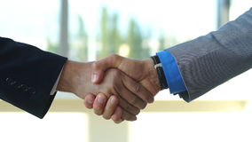 Two business men shaking hands slow motion. Two business men shaking hands in office stock video footage