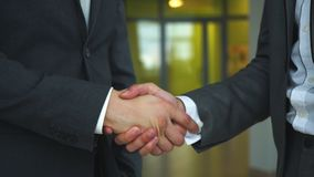 Two business men shaking hands slow motion. Two young businessmen shaking hands in office stock video footage