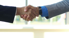 Two business men shaking hands slow motion. Two young businessmen shaking hands in office stock footage