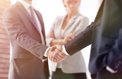 Two Business men shaking hands. While team smiling at office Royalty Free Stock Images