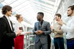 Two business men shaking hands while their colleagues applauding and smiling. Young business partners applauding to reporter after listening report at seminar Royalty Free Stock Photos