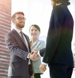 Two Business men shaking hands. While team smiling at office Royalty Free Stock Photo