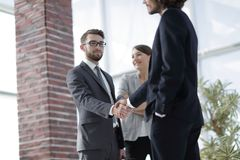 Two Business men shaking hands. While team smiling at office Stock Image