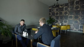 Two business men sit in a stylish cafe at a table. They talk among themselves and condemn the menu for a business breakfast. During lunch, entrepreneurs decide stock footage