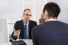 Two business men sitting in the office: meeting or job interview. Two businessman sitting in the office: meeting or job interview situation Stock Images