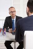 Two business men sitting in the office: meeting or job interview. Two businessman sitting in the office: meeting or job interview situation Royalty Free Stock Photo